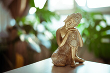 Decorative Golden Bronze Buddha Statuette With Green Monstera Plant In Room Decor On The Background. Meditation And Relaxation Ritual. Exotic Massage. Selective Focus. Copy Space.