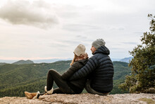 Couple Looking At Mountains Against Sky While Sitting On Observation Point
