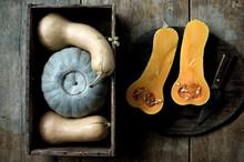 Butternut Pumpkins (Cucurbita Moschata) Cut In Halves And Crown Prince Pumpkin (Cucurbita Maxima) Against Rustic Background