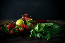 Studio Shot Of Fresh Rhubarb Stalks, Strawberries And Single Lemon