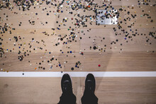 Feet With Black Sneakers And Wooden Floor With White Line And Thousand Of Colored Buttons