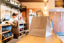 Take Out Food Kept In Brown Paper Bag On Bar Counter During Pandemic