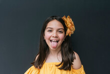 Close-up Of Girl Wearing Yellow Headband Sticking Out Tongue Against Black Background