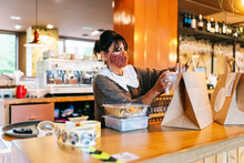 Female Owner In Mask Attaching Receipt On Brown Paper Bag On Counter At Restaurant