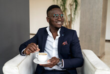Smiling Male Professional Looking Away While Holding Coffee Cup In Hotel Lobby
