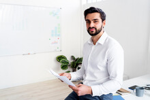 Handsome Male Entrepreneur Holding Paper Document While Sitting At Work Place