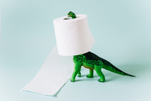 Diplodocus Dinosaur Toy With A Roll Of Toilet Paper Around The Neck On Mint Green Background