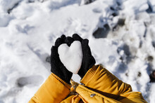 Girl's Hands Holding Heart Shaped Snow In Park