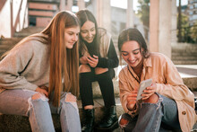 Smiling Teenage Girl Showing Mobile Phone To Friends While Sitting On Steps In City