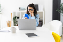 Smiling Businesswoman Using Mobile Phone While Sitting At Office