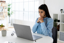 Businesswoman Wearing Headset Using Laptop While Sitting With Hand On Chin At Office