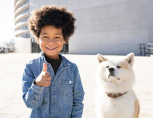 Smiling Boy Gesturing Thumbs Up While Standing By Dog Sitting On Footpath