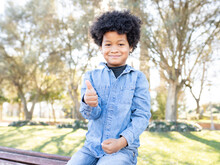 Smiling Boy Showing Thumbs Up While Sitting At Park