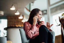 Female Professional Gesturing While Talking On Phone Call In Cafe