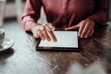 Businesswoman's Hand Using Digital Tablet At Table In Cafe