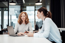 Female Professionals Discussing Over Laptop In Illuminated Board Room At Office