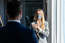 Businesswoman Wearing Protective Face Mask Standing With Hand On Chest While Greeting Colleague In Office