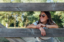 Smiling Young Woman Wearing Sunglasses Leaning On Wooden Fence In Forest