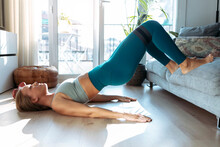 Woman Practicing Bridge Position While Exercising At Home