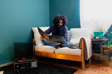Bearded Man With Long Hair Reading Record Cover While Sitting On Sofa At Home