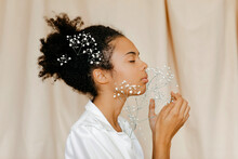Woman With Eyes Closed Smelling White Flowers By Beige Curtain