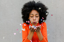 Afro Young Woman With Eyes Closed Blowing Confetti Against Wall