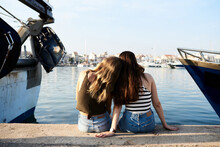 Blonde Girl Leaning Head On Shoulder Of Her Friend On Pier