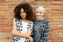 Beautiful Smiling Friends In Animalistic Outfit On Brickwall