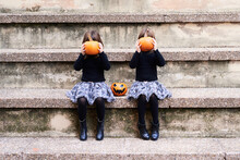 Two Playful Girls With Pumpkins.