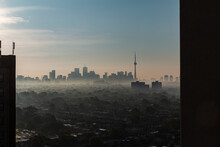 Skyline Of Toronto With Its CN Tower, Seen From A Skyscraper In The District The Junction On A Foggy Autumn Morning During Sunrise