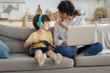Nervous Freelancer Mother Sitting On Couch At Home Office During Lockdown, Working On Laptop, Asks Not To Make Noise. Little Child Distracts From Work, Showing Tablet, Asking Attention From Busy Mom.
