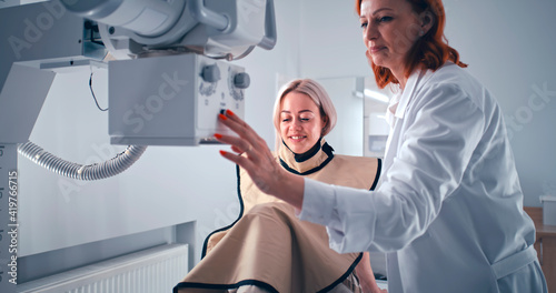 Tela Female patient speaking with doctor during X ray scanning preparation