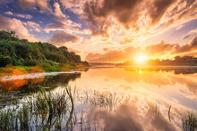 Sunset On The River With Cloudy Skies Reflected In The Water And Willows Growing Along The Shore In Summer.