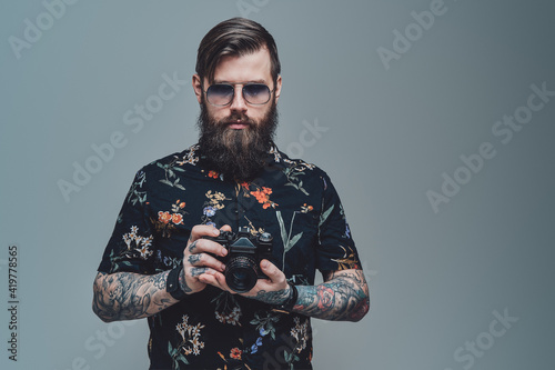 Obraz Successful hipster person with bearded face and modern coiffure posing in gray background holding photo camera. - fototapety do salonu
