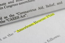 Closeup Of The Documents Of Both The Cares Act (Coronavirus Aid, Relief, And Economic Security Act) And The American Rescue Plan Act Of 2021.
