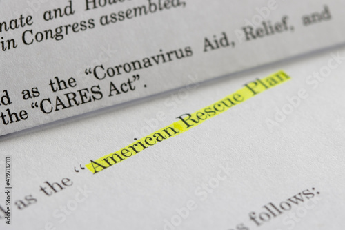 Photo Closeup of the documents of both the Cares Act (Coronavirus Aid, Relief, and Economic Security Act) and the American Rescue Plan Act of 2021