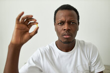 Isolated Image Of Frustrated Young African American Male Wearing White T-shirt Holding Pill Between Thumb And Fore Finger Looking At Camera With Doubtful Indecisive Facial Expression, Frowning