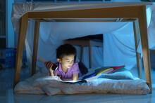 Asian Preschool Boy Child To Make A Camp To Play Imaginatively And Reading Book By Flashlight  In Living Room At Home..