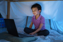 Asian Boy Child To Make A Camp To Play Imaginatively Watching A Film On Laptop In The Darkness Of The Camp In Living Room At Home.