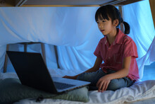 Asian Girl Child To Make A Camp To Play Imaginatively Watching A Film On Laptop In The Darkness Of The Camp In Living Room At Home.