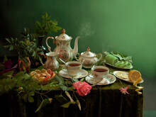 Tea Still Life. Two Cups Of Tea, A Teapot, Flowers, Lemon And Sweets On A Table With A Green Tablecloth.