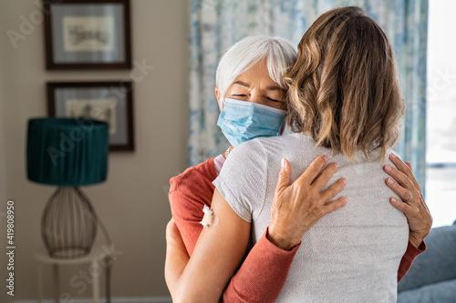 Obraz na plátně Grandmother hugging daughter after covid19 vaccination