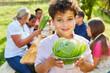 Kind mit Salatkopf im Kochkurs für gesunde Ermährung