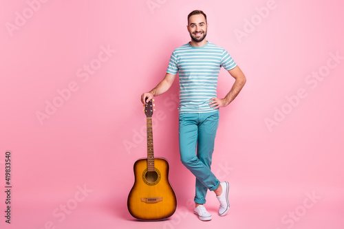 Obraz Full length body size view of attractive cheerful guy holding string guitar country style singer isolated over pink color background - fototapety do salonu