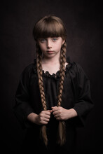 Classic Painterly Dark Studio Portrait Of A Girl In Black Dress Holding Her Long Brown Braids