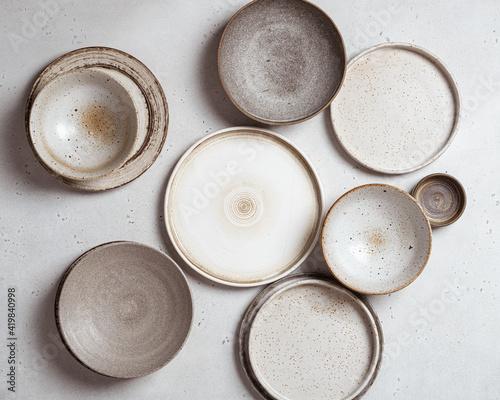 Valokuvatapetti handmade ceramics, empty craft ceramic plates on light background top view