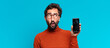 young crazy bearded man confused expression. smart phone concept