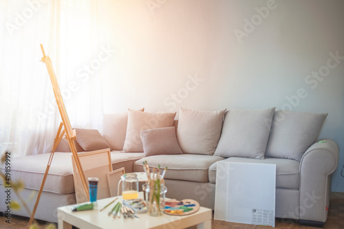 Obraz Creative artist workplace no people hobbies. Painting at home of a freelance artist. Easel, canvas, brushes, pencils, paints with albums on the table. The interior in the home of the artist - fototapety do salonu