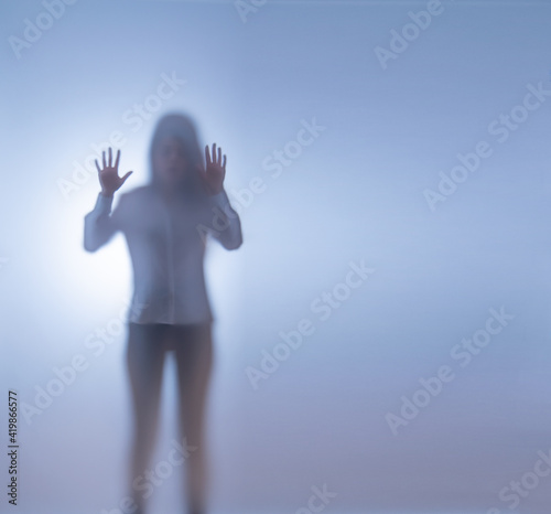 Photo A young woman stands behind frosted glass