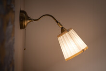 A Classic Design Luxury Reading Electric Lighting Lamp During Turn-on In Warming Light Tone Shade Which Is Installed In Bedroom Wall. Close-up And Selective Focus. Photo Contain Shadow And Dark Area.